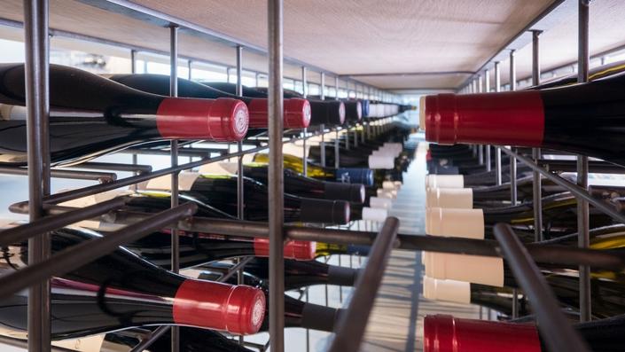 Unterseite vom Präsentationstisch als Weinflaschenregal genutzt